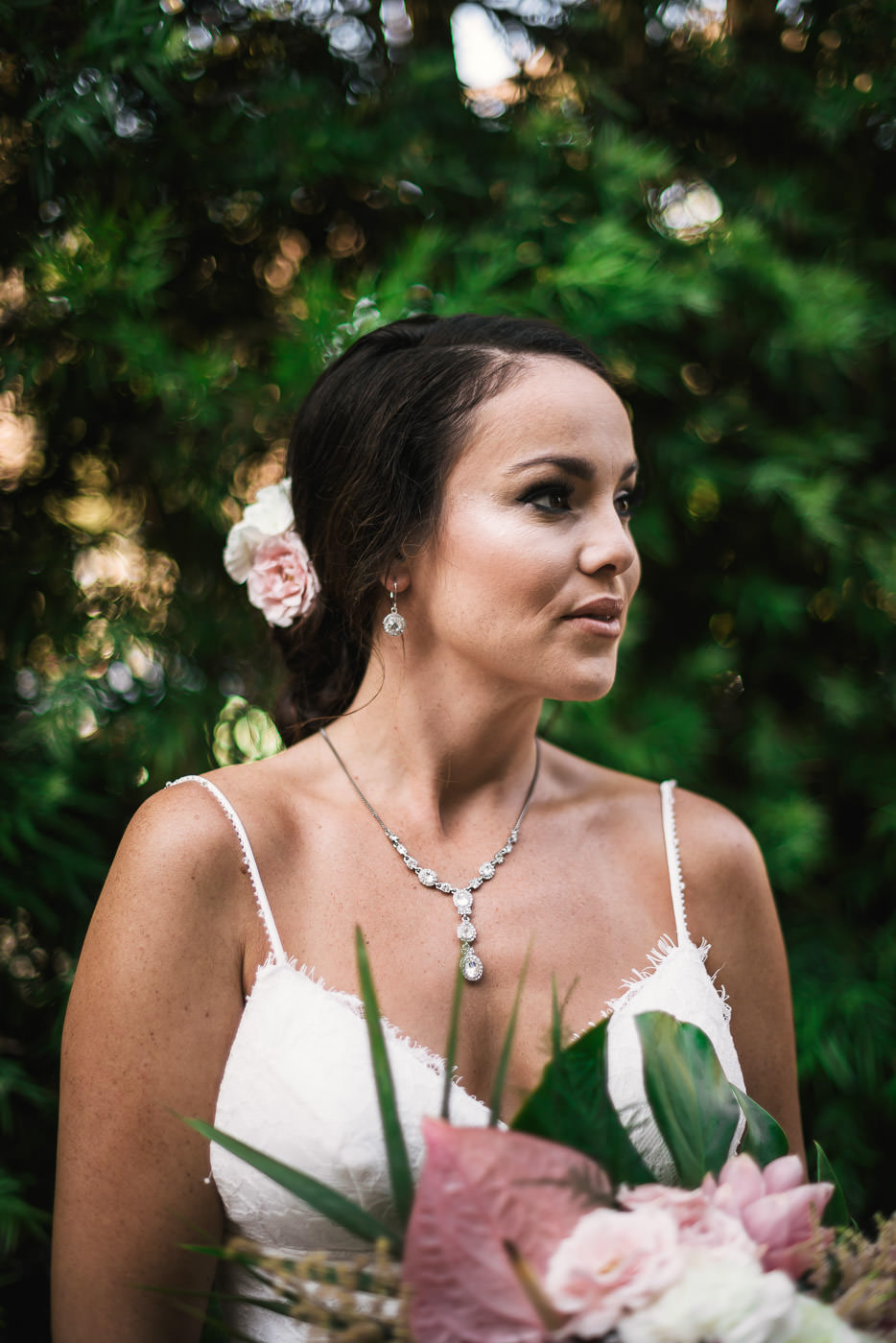 Beautiful portrait of a bride in front of green folliage.