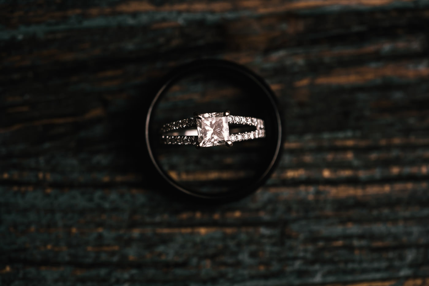 Overhead photo of a diamond wedding ring sitting inside the grooms ring.