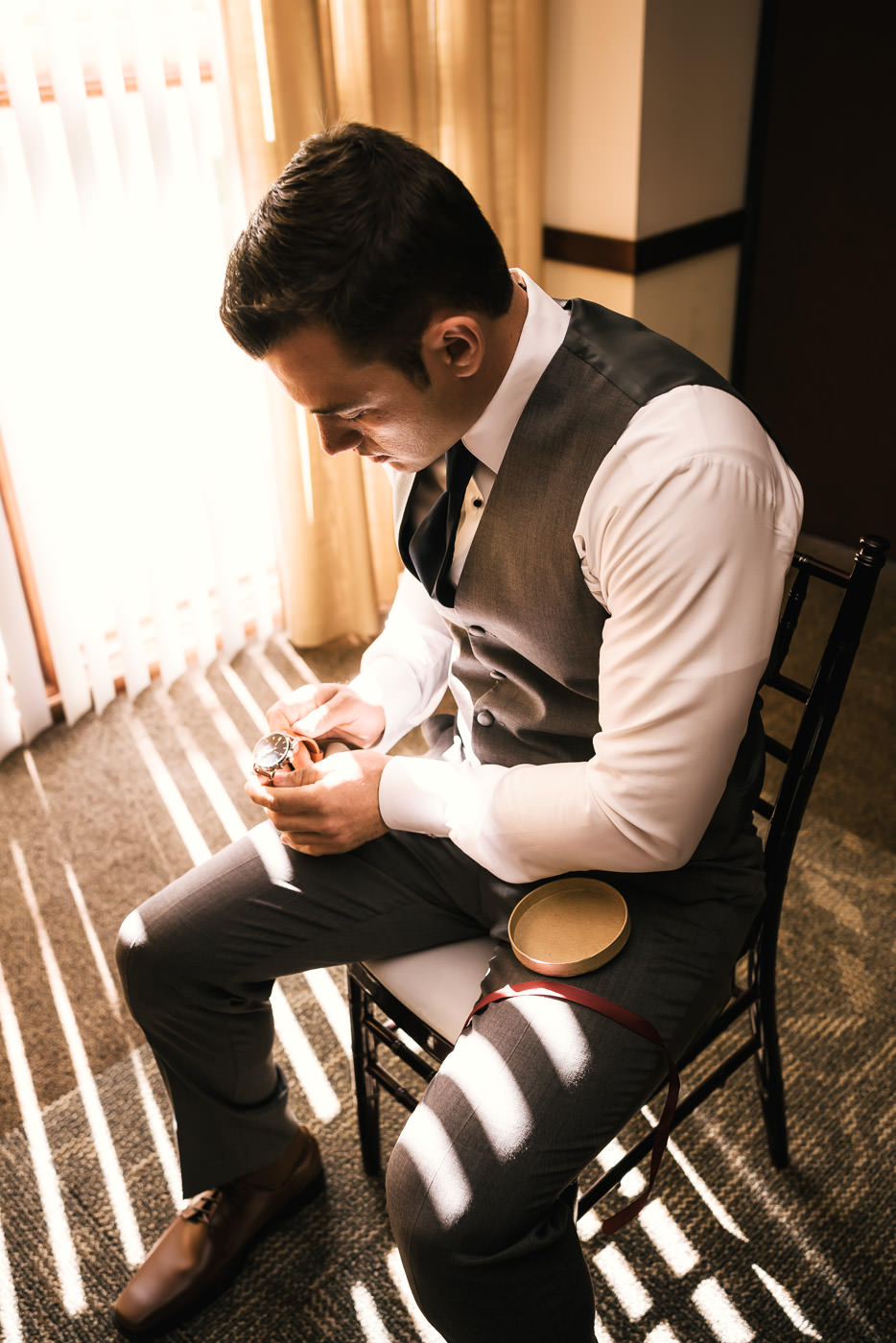 Groom sits in the light of the window and opens a gift from his bride.