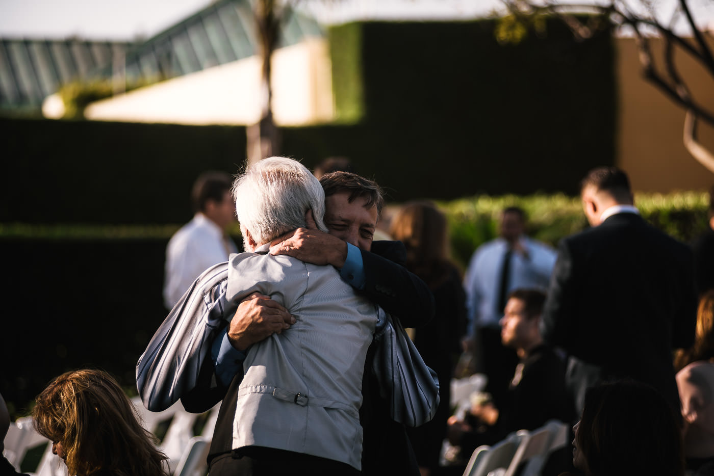 Father of the groom hugs a guest moments before the ceremony starts.