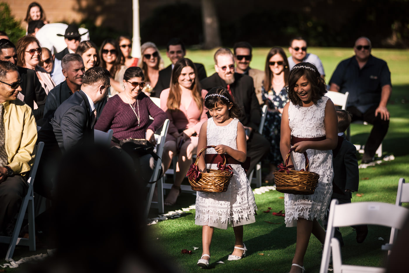 Adorable flower girls in lace dresses walk down the aisle at the Alta Vista Country Club.