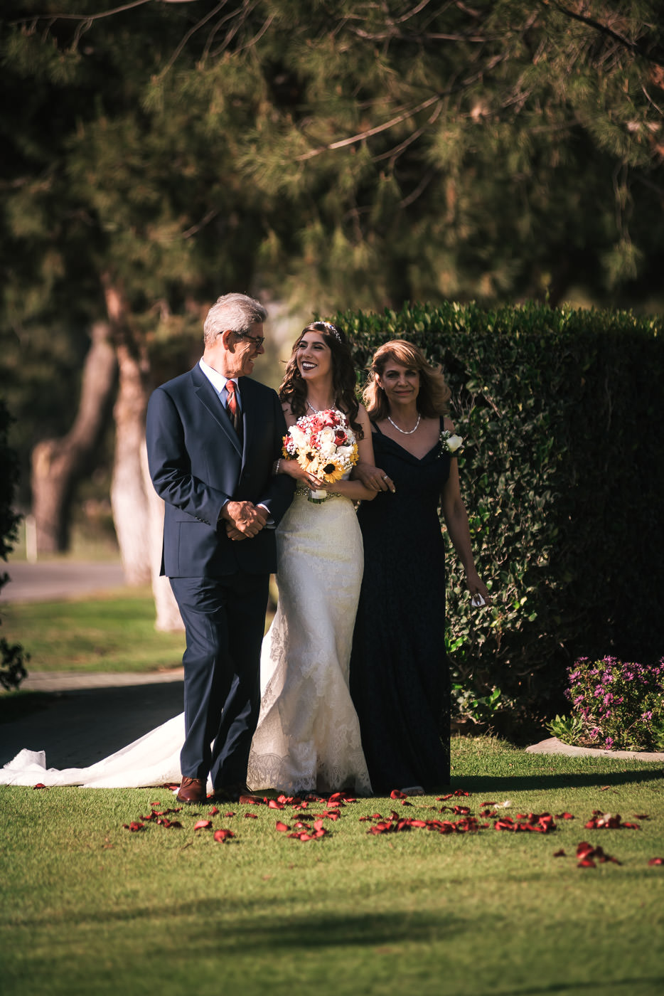 Bride walks down the aisle with her mother and father at her Alta Vista Wedding.
