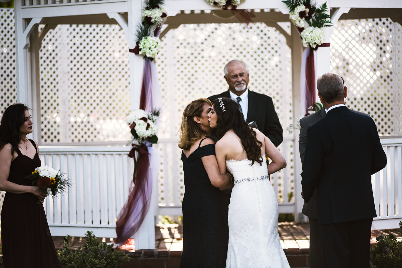 Bride gives her mother a kiss while the groom shakes her father's hand.