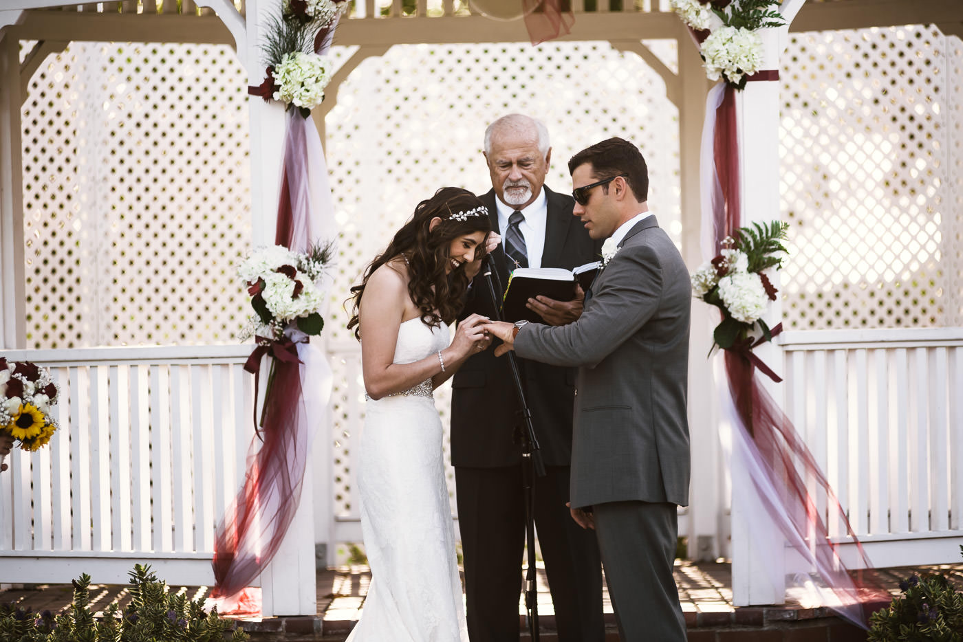 Beautiful bride places the wedding ring on her husbands finger during the marriage ceremony.