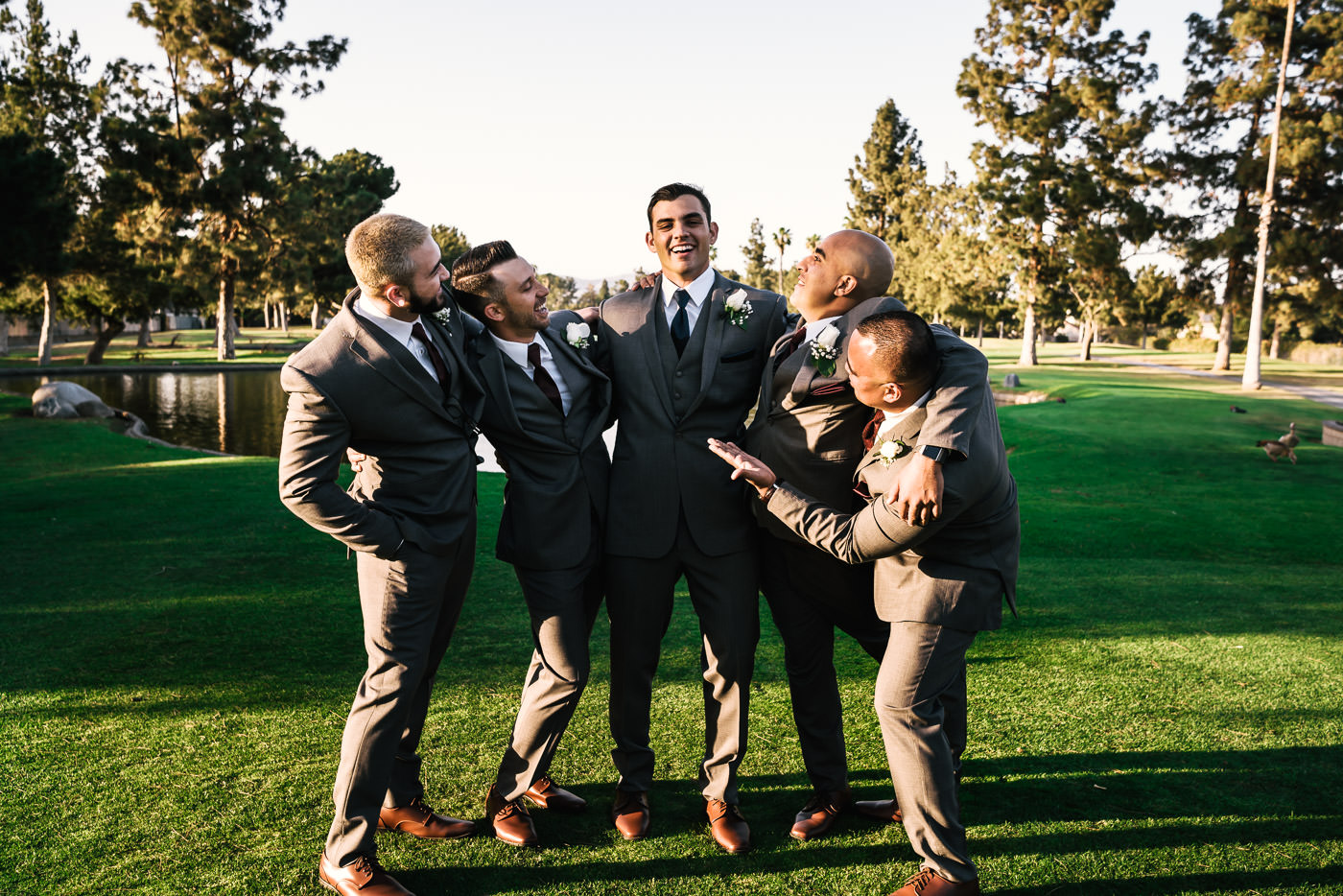 Groomsmen poses with the groom and share a laugh.