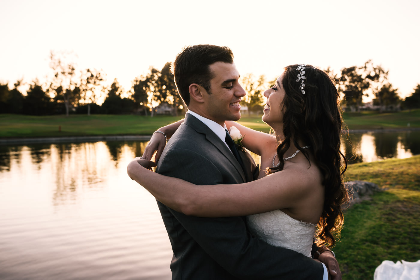 Couple holds each other close as the sun sets on the pond behind them.