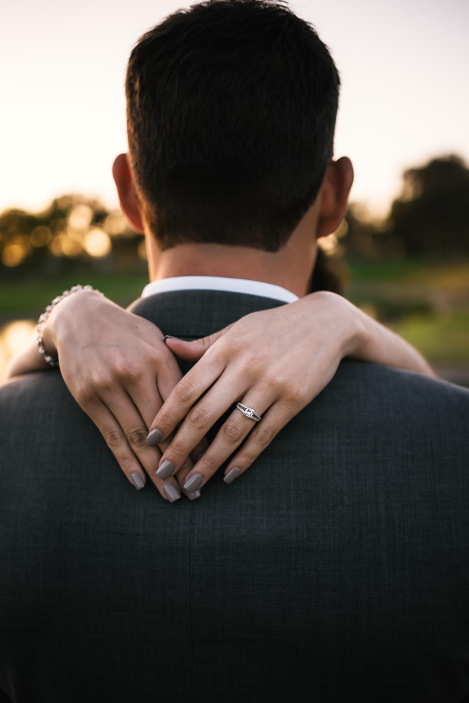 Bride shows off her stunning wedding ring and chic grey nails.
