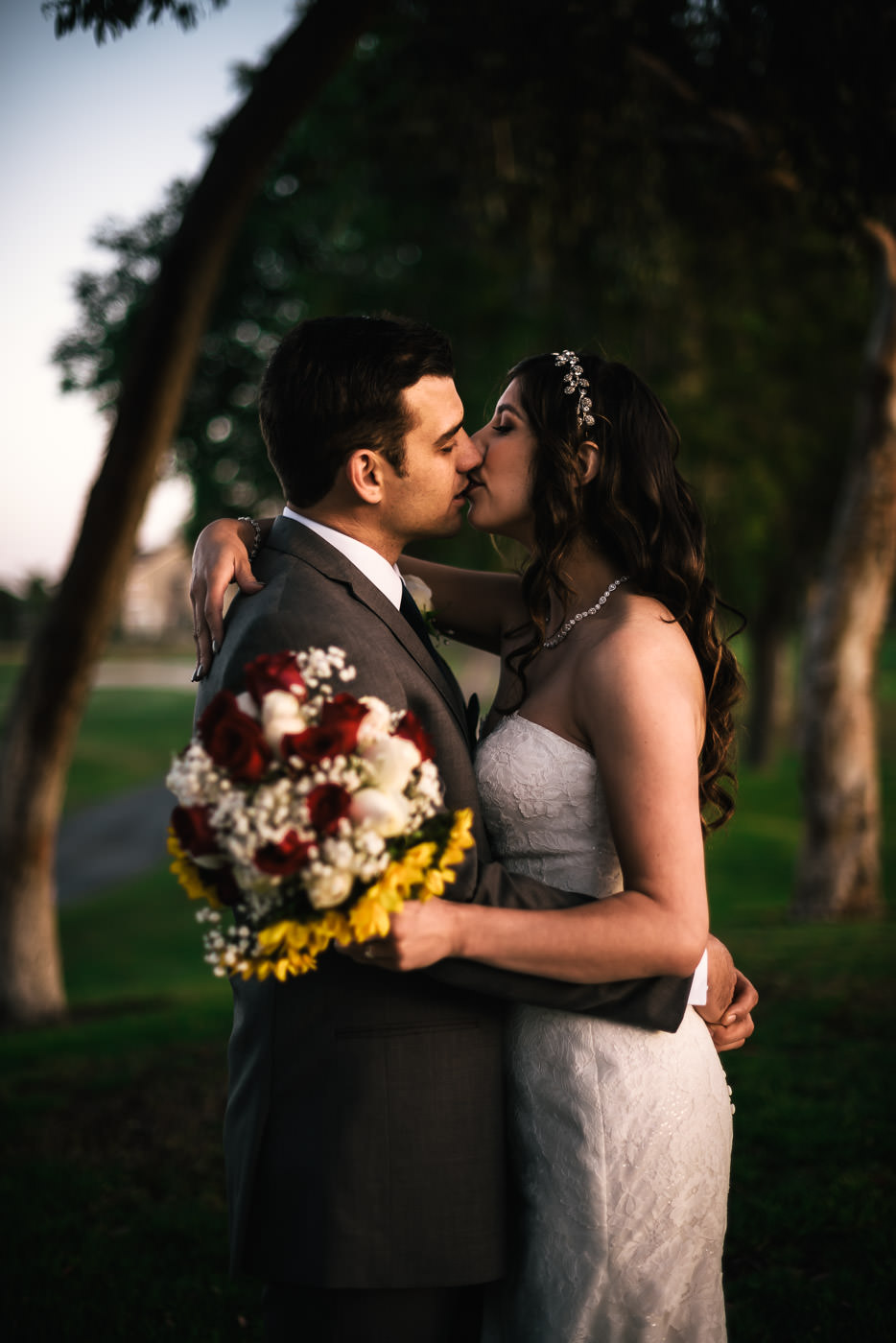 Bride and groom have a romantic kiss in the golden light of the setting sun.