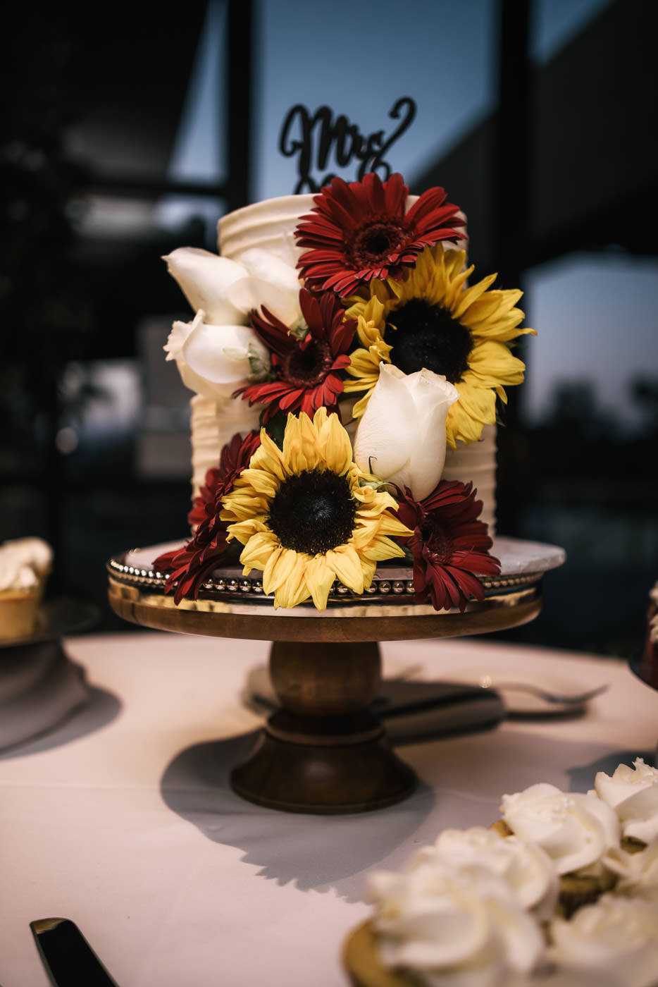 White wedding cake with yellow sunflowers and red daisies.
