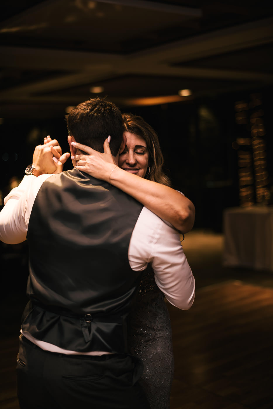 Mother holds her son close as she dances with him at the reception.