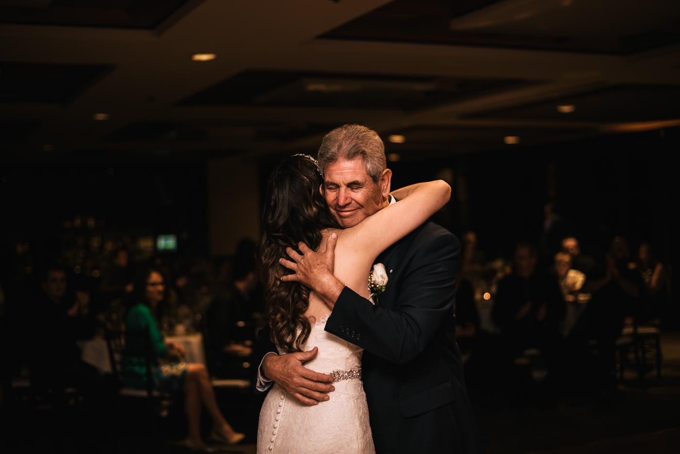 Father hugs his daughter tightly at her reception.