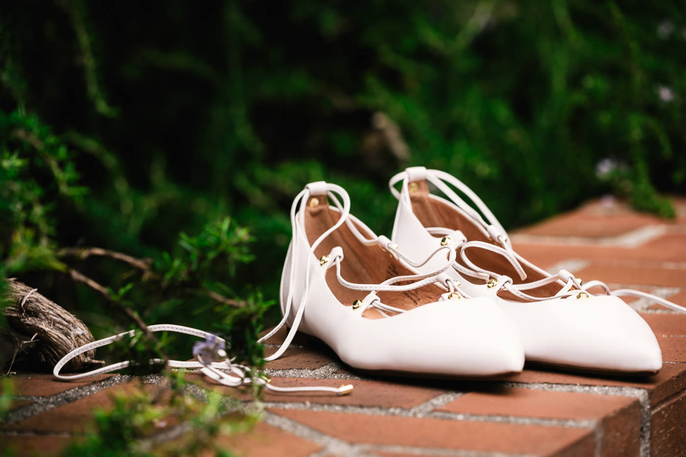 Bride's white shoes sit on a brick wall.