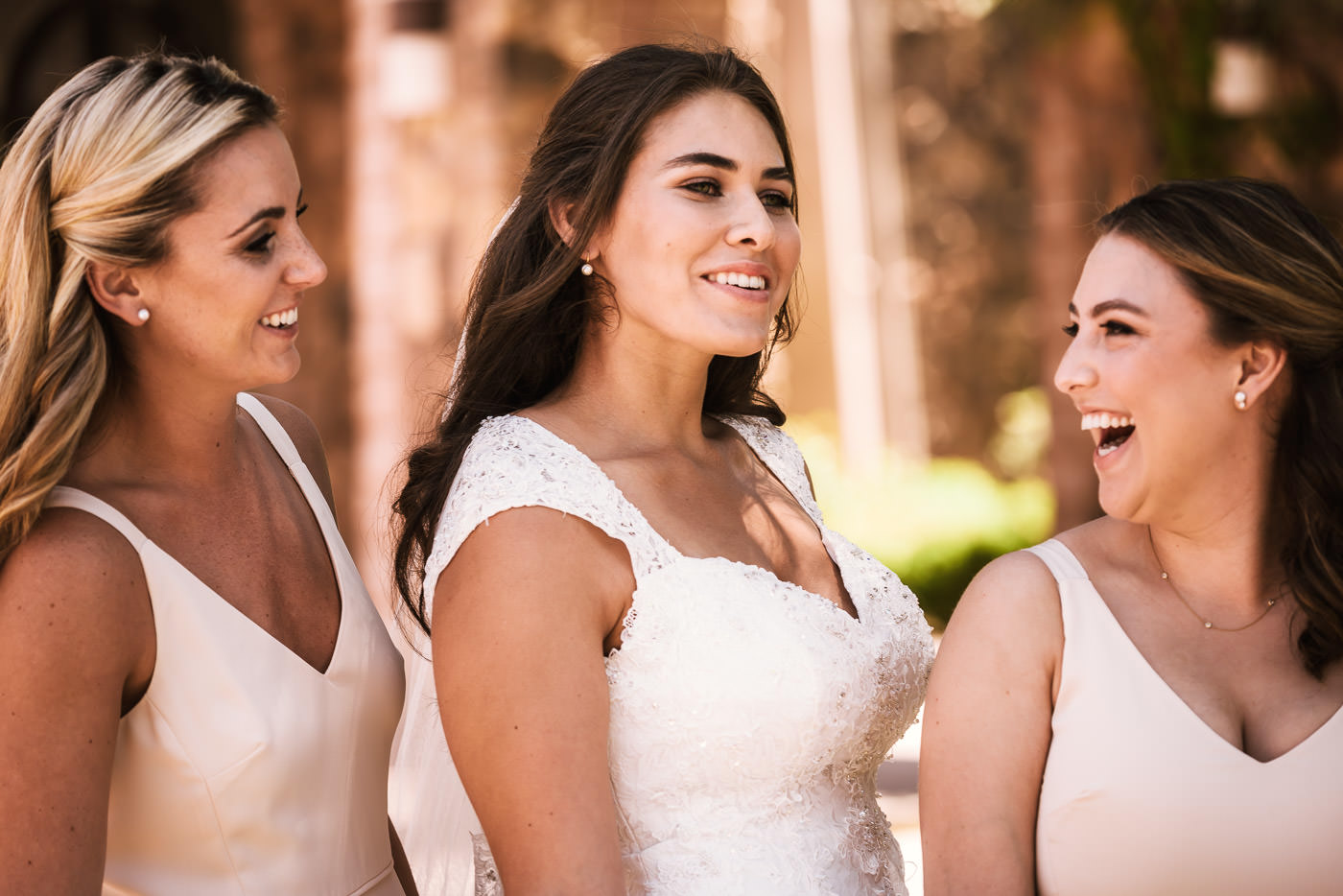 Bridesmaids laugh with the bride before the ceremony.