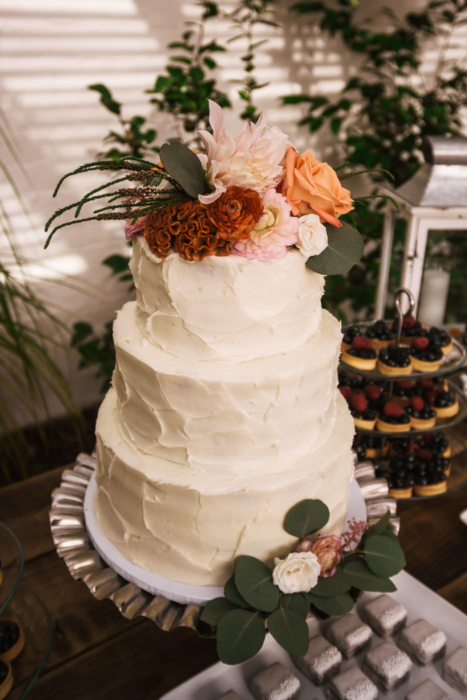 Three tiered wedding cake with flower topper and eucalyptus details.