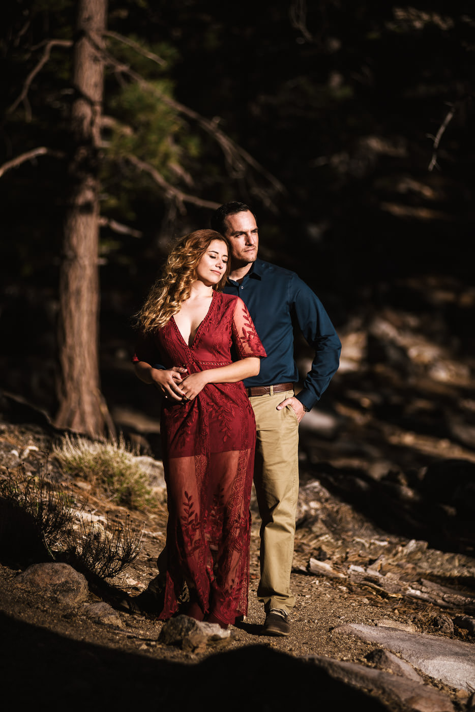 Woman leans against her future husband as the sun sets on the forests of Mt. San Jacinto.