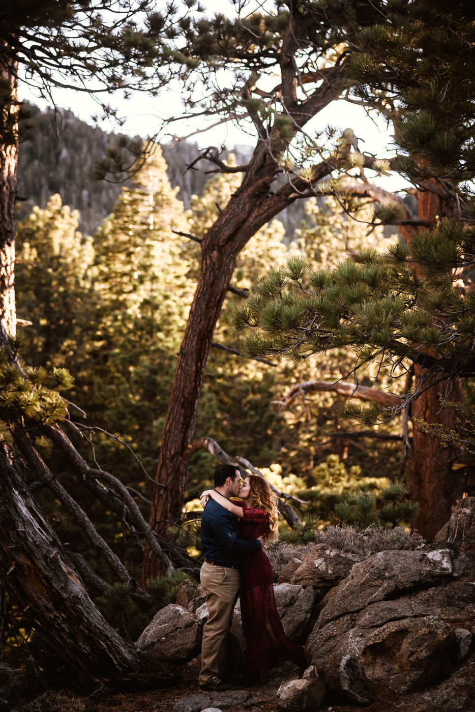 Beautiful portrait of a couple kiss at sunset in the woods of California's mountians.