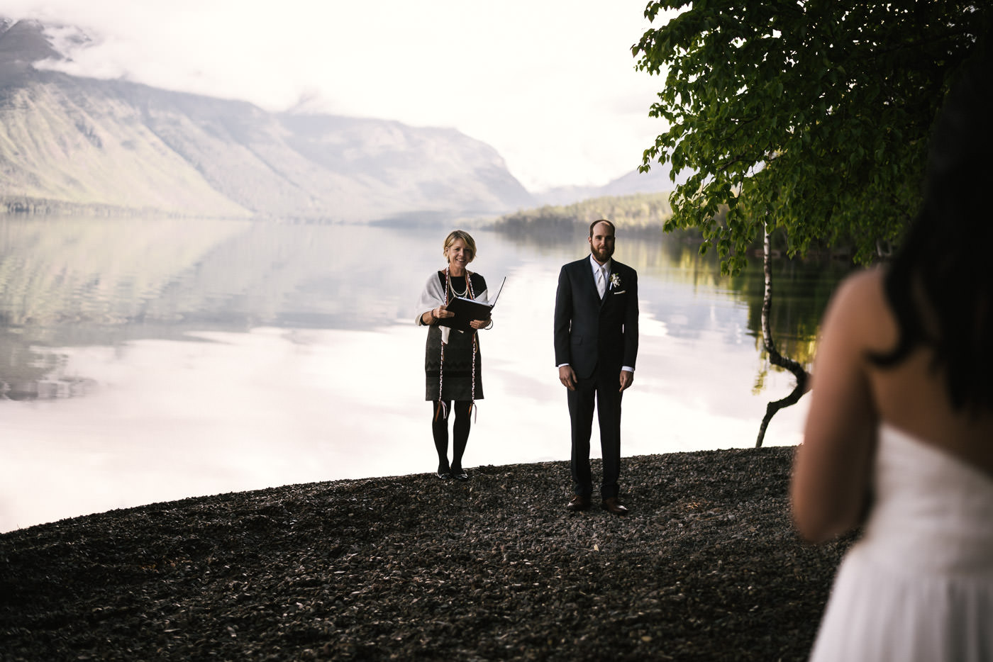 Groom smiles as he sees his bride approach for their wedding ceremony in Glacier National Park.