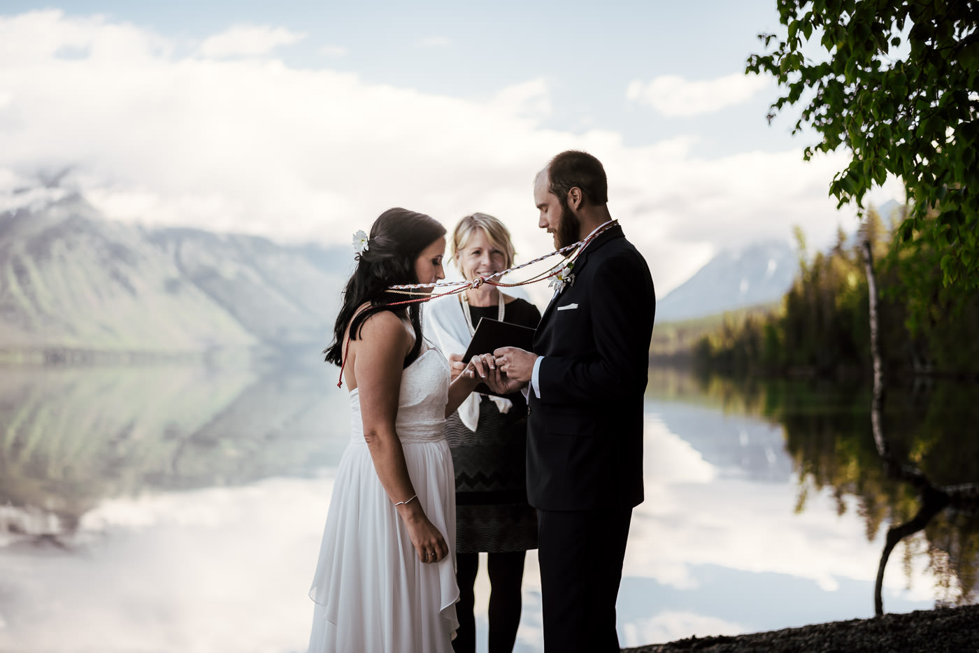 Groom places wedding ring on his new wife's finger at their Montana elopement.