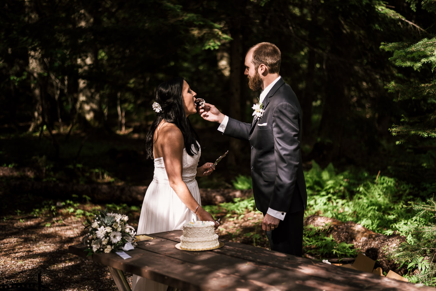 Husband feeds his new wife a piece of cake at their Montana wedding.