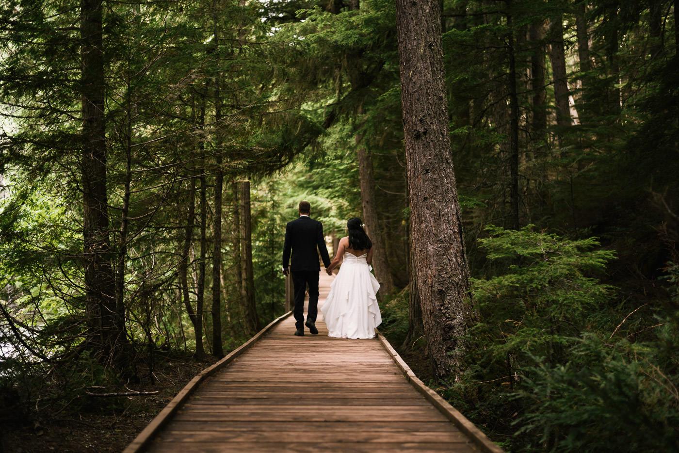Newlyweds walk down the boardwalk through the trail of cedars.