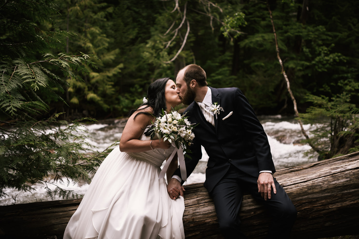 Couple in love sits on a fallen cedar tree and kiss in front of a raging river.