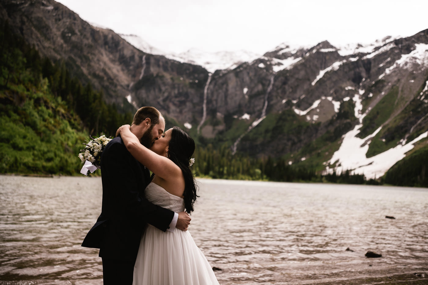 Newlyweds kiss before Avalanche Lake in Glacier National Park.