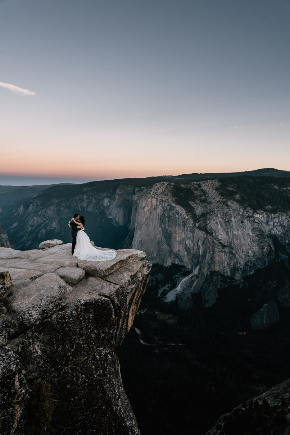 Eloping couple stands on the ledge of the Yosemite valley for an unforgettable wedding photo.