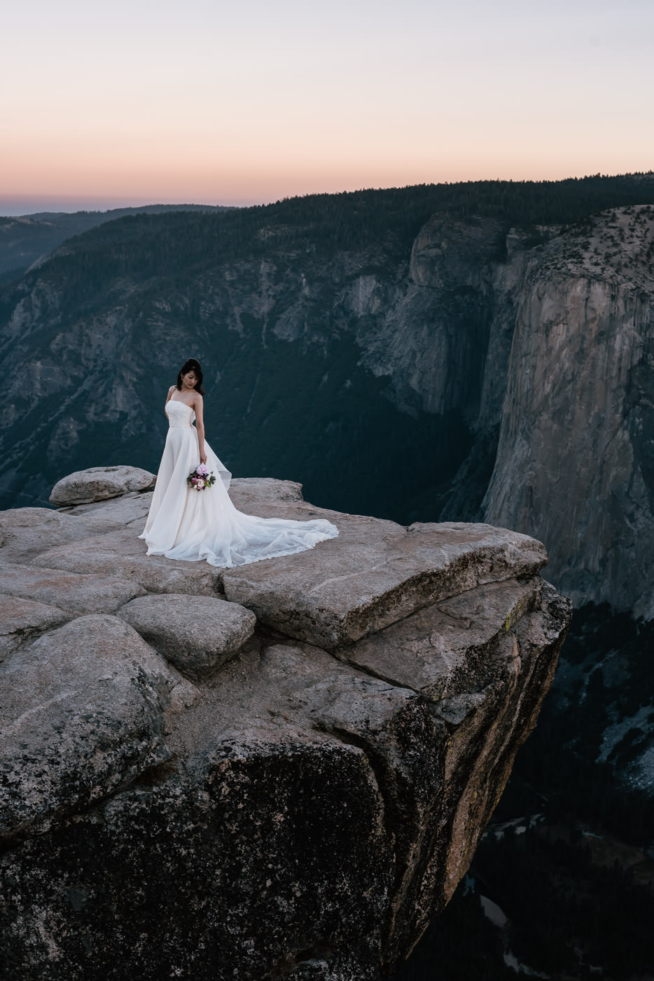 Beautiful bride poses in her white wedding dress on the grey granite cliffs of Yosemite's southern rim.