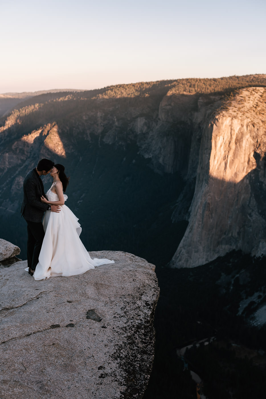 Groom is pulled in close to his wife for a passionate kiss in the wilderness of the national parks.
