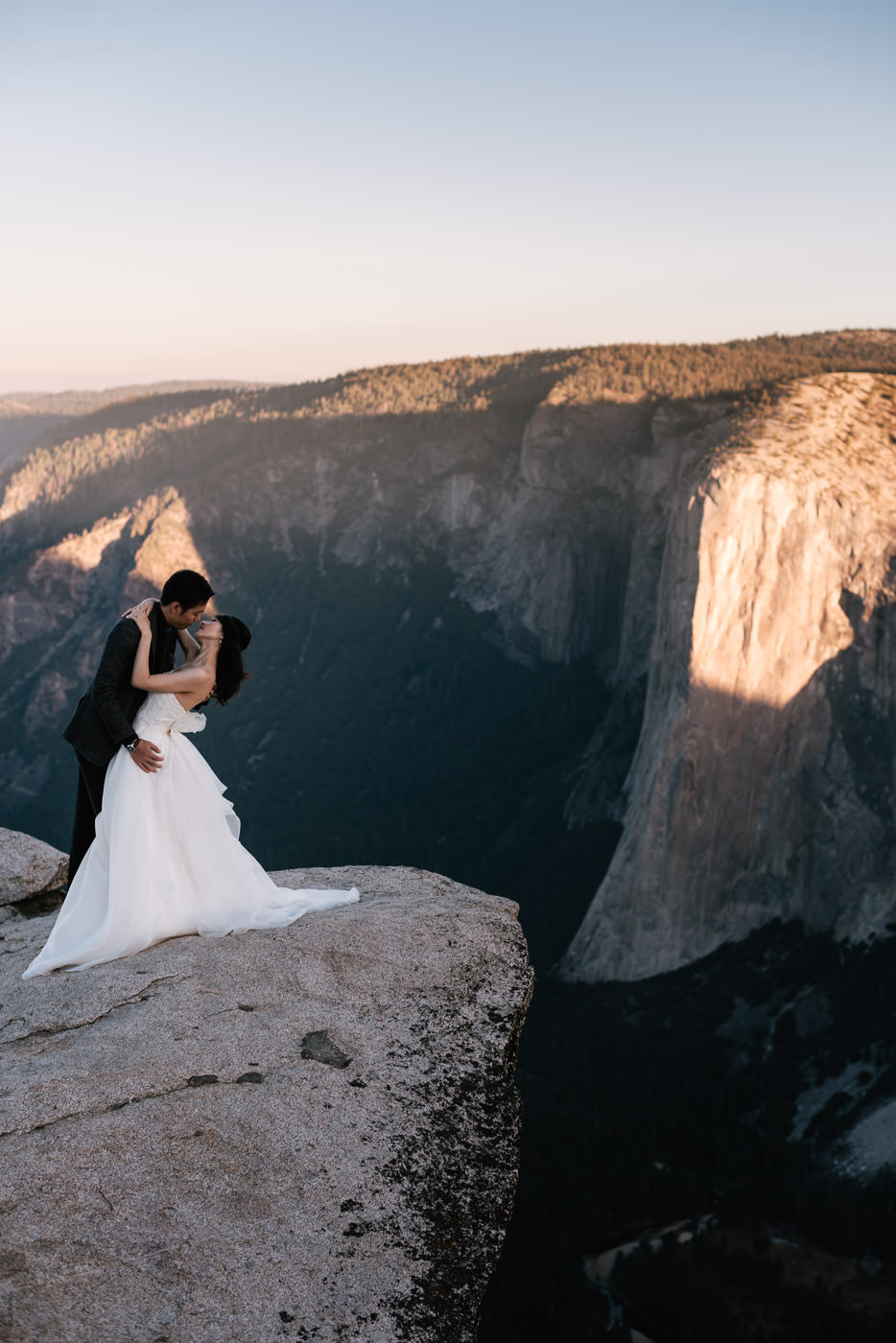 Couple kisses at Taft Point as the sun rises on El Capitan in the background.