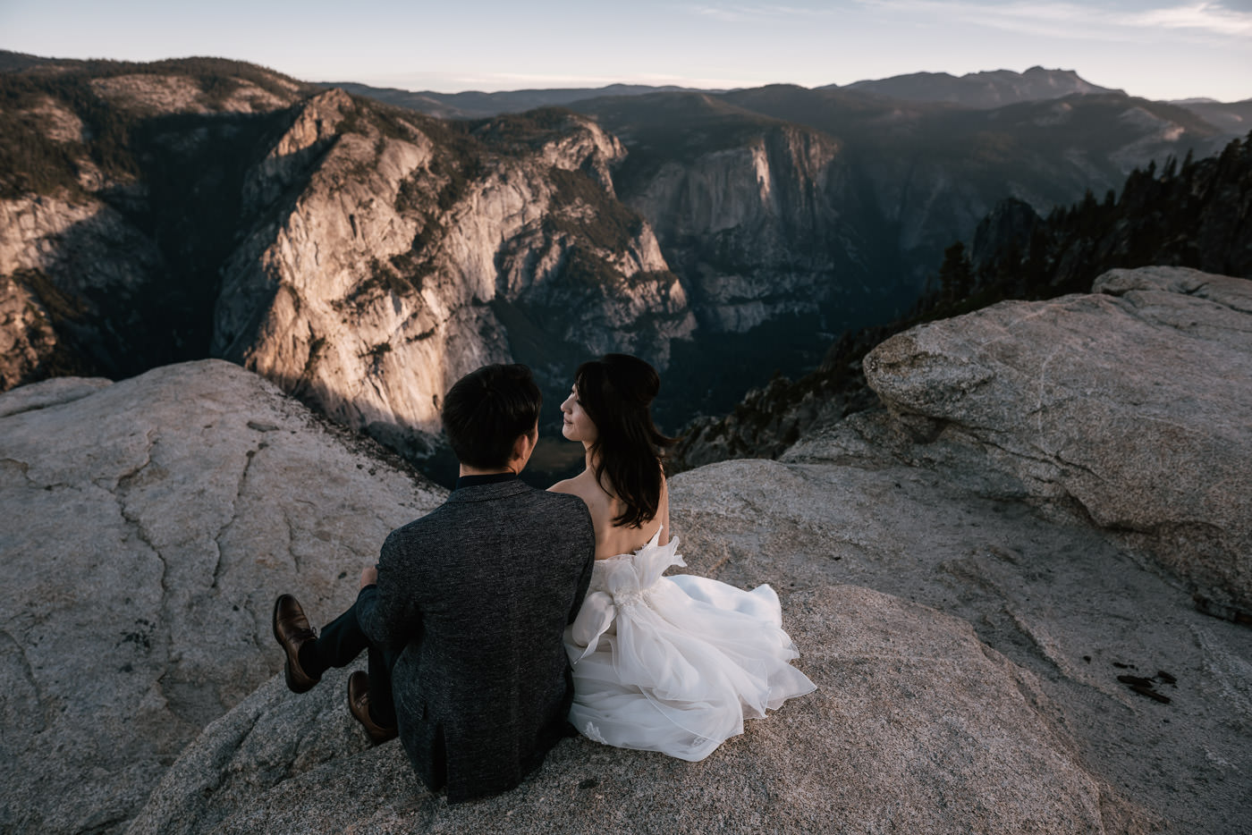 Bride and groom sit on the granite steps of Taft Point while the sun rises on the valley below.
