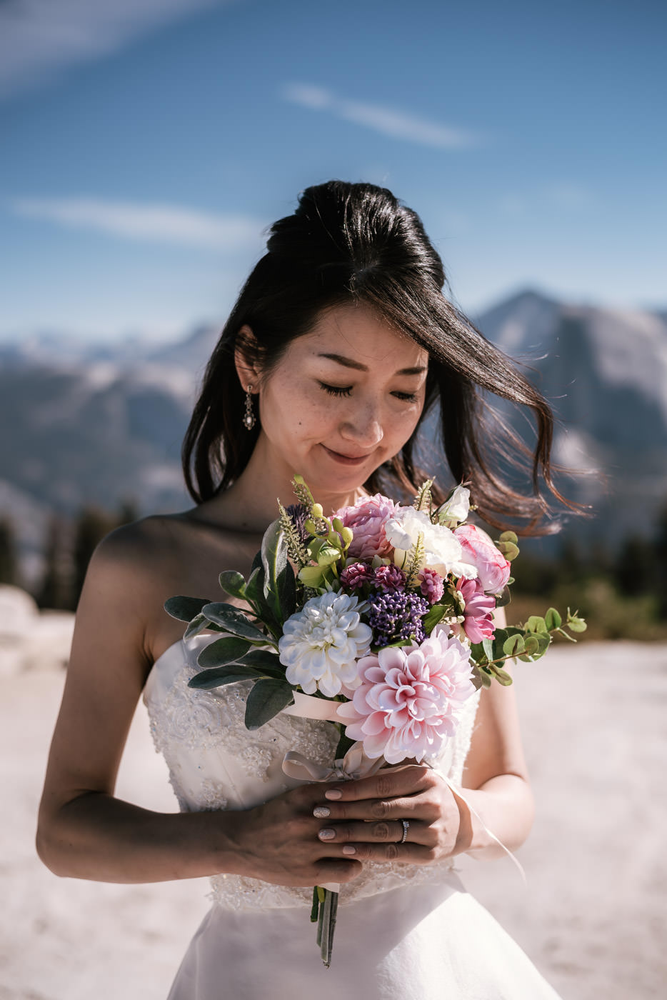 Bride holds up her bouquet and smells the beautiful flowers.