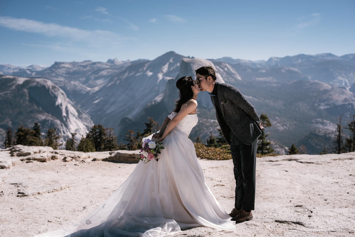 Bride and groom lean in togeather for a sweet kiss with the sprawling vista of the Sierra in the background.