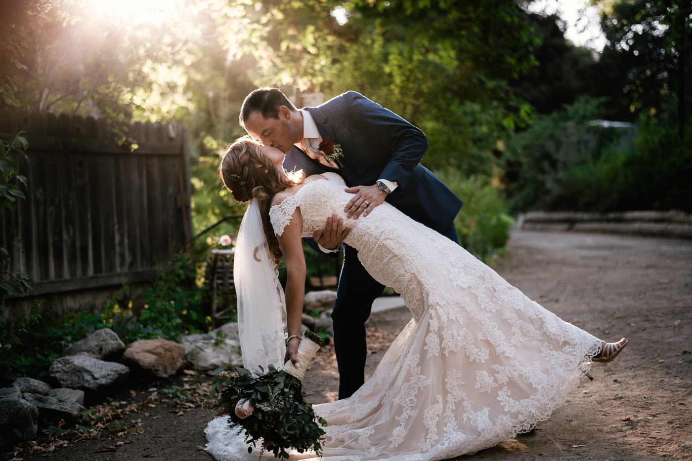 Groom dips his bride and gives her a tender kiss at The Homestead.