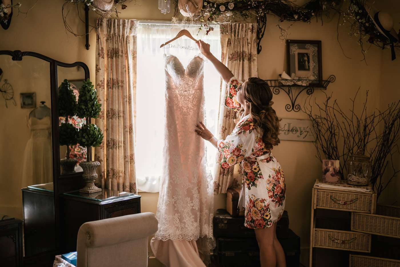 Bride reaches up to grab her wedding dress before the big event.