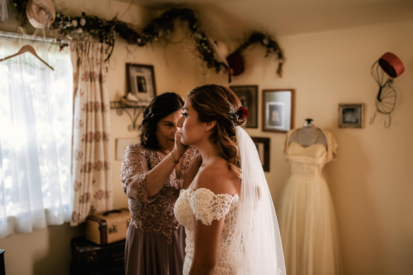 Mother of the bride puts earrings on her daughter before her wedding.