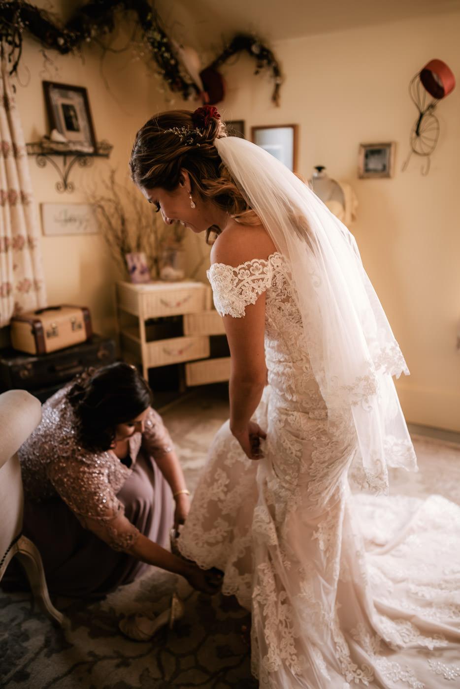 Bride's mother helps her with her heels.