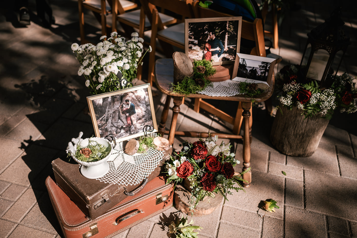 Old suitcases, and flower bouquets showcase the couples engagement photos at their ceremony.