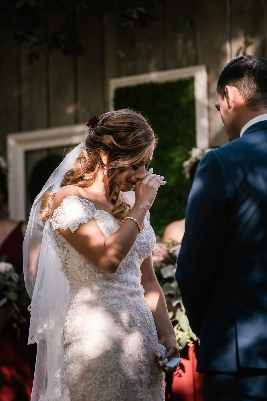 Bride tears up as she listens to her husband's marriage vows.