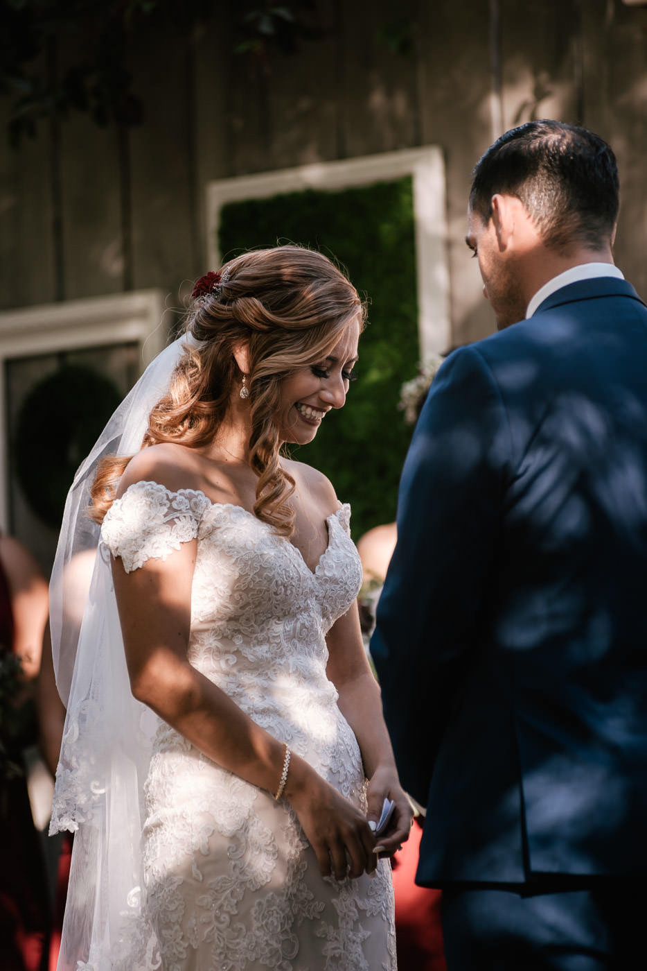 Bride is all smiles as her husband makes his marriage vows at their rustic wedding at The Homestead.