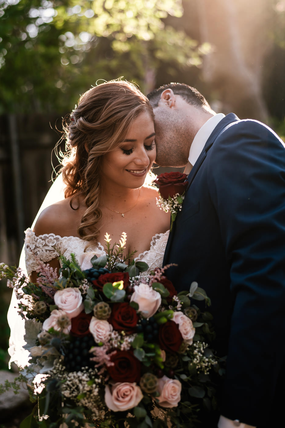 Groom whispers in his new brides year and makes her smile.