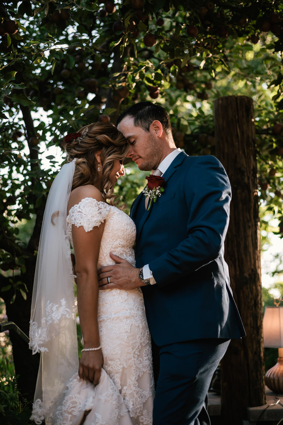 Groom rests his forehead agaisnt his new wife and pulls her in close for a quiet moment.