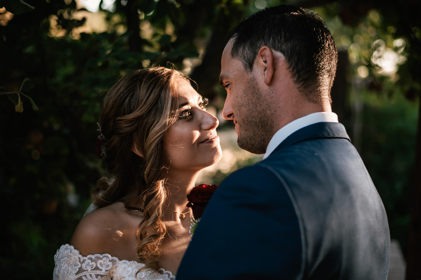 Couple stares deep into each others eyes for a sweet moment under the apple tree at The Homestead.