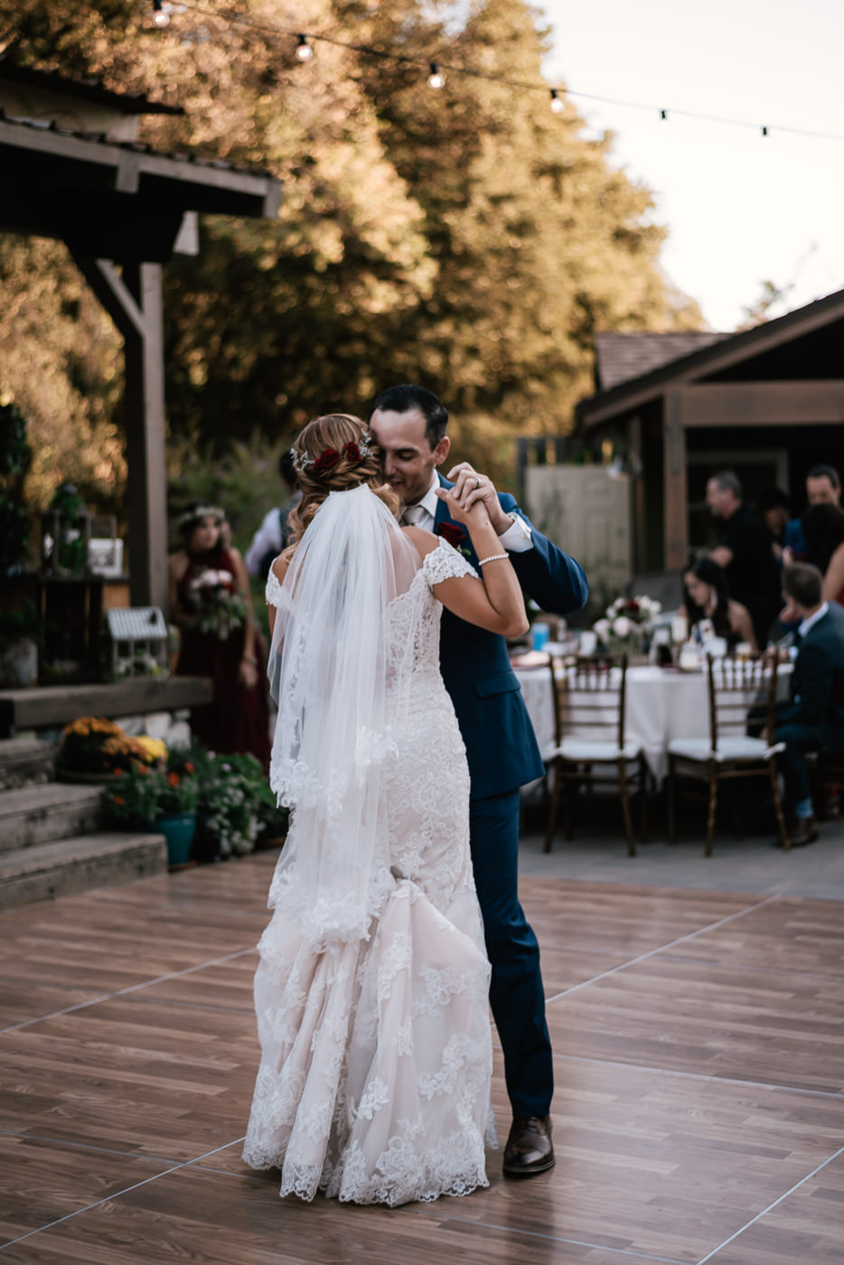 Groom whipsers into his new wife's ear as they enjoy their first dance.