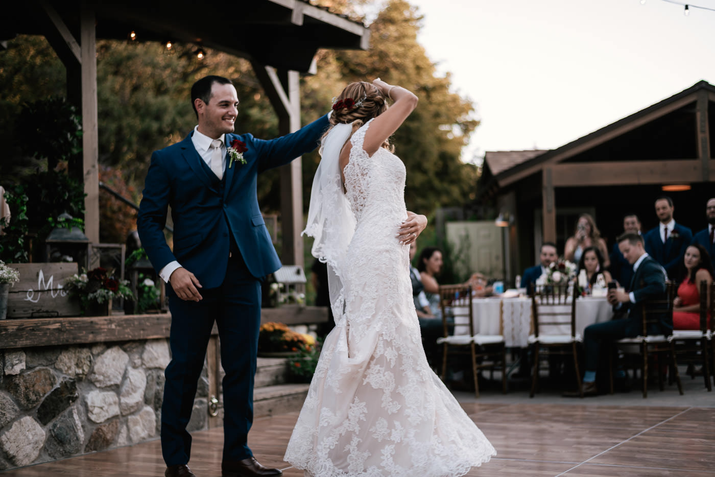 Groom gives his wife a twirl on the dance floor at their wedding reception at The Homestead.