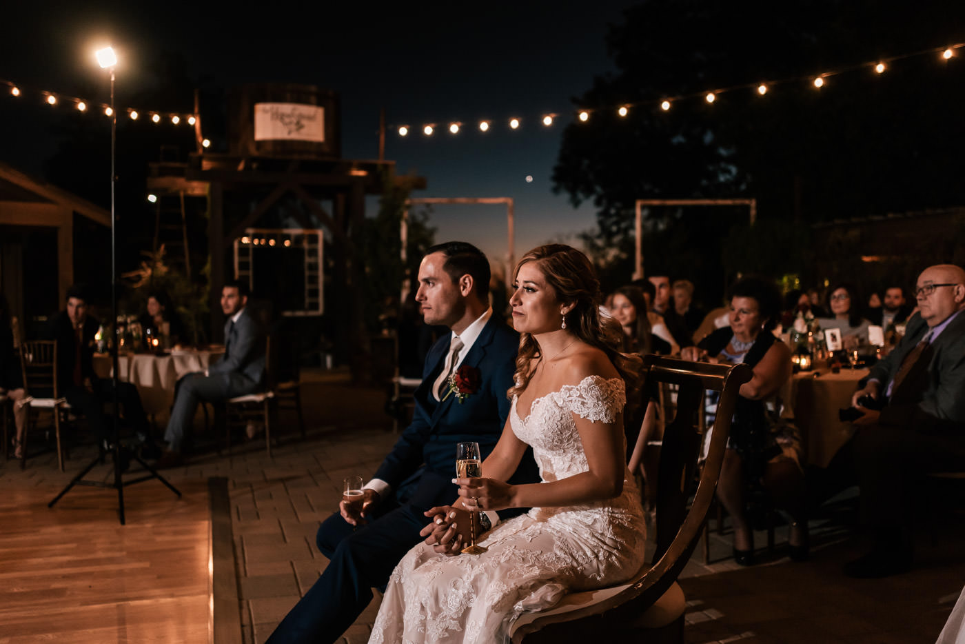 Newlyweds listen intently to the speeches at their reception.