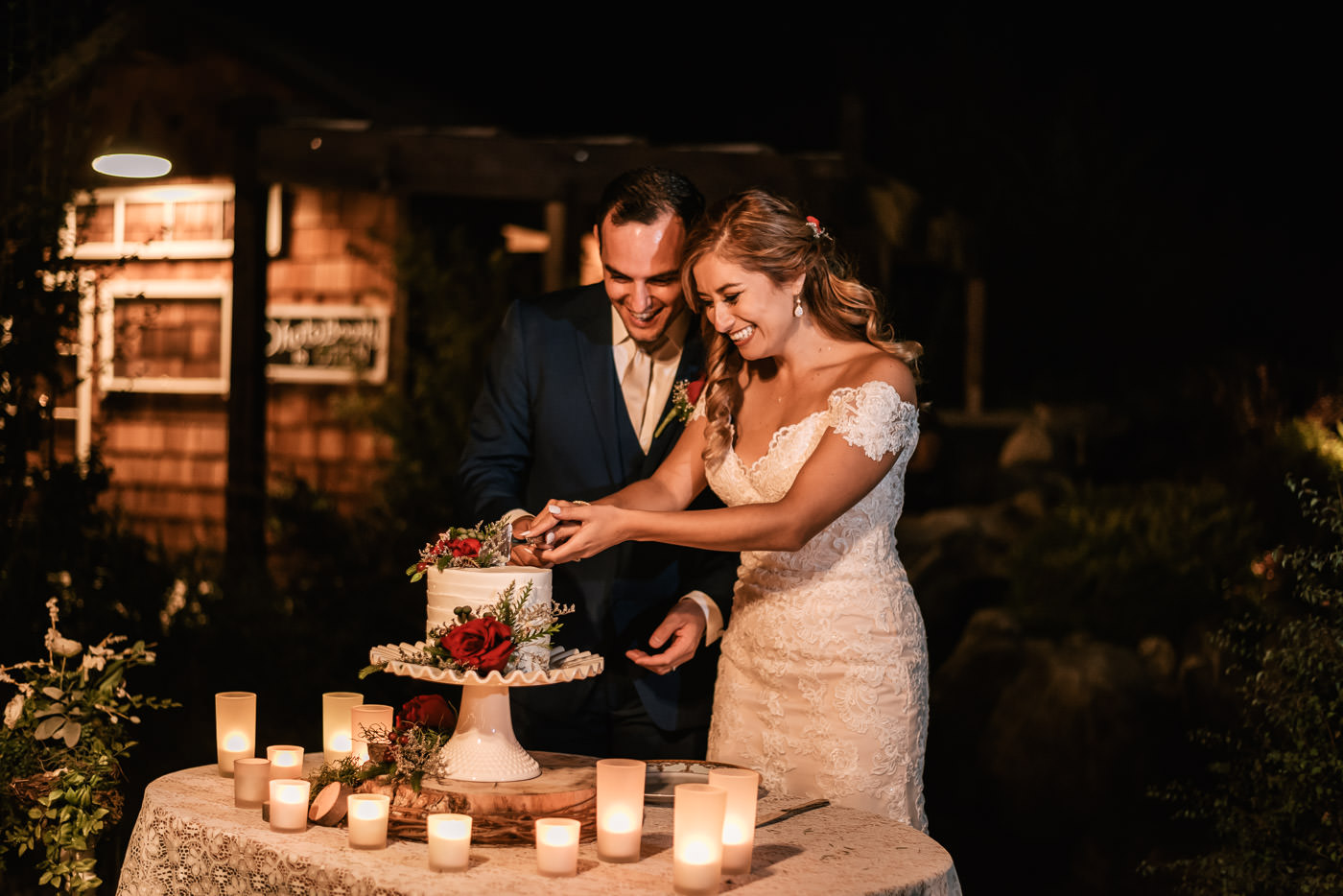 Bride and groom prepare to cut the cake at their reception at The Homestead.
