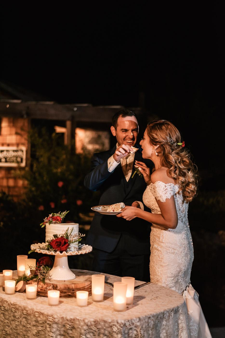 Groom feeds his bride a piece of wedding cake.