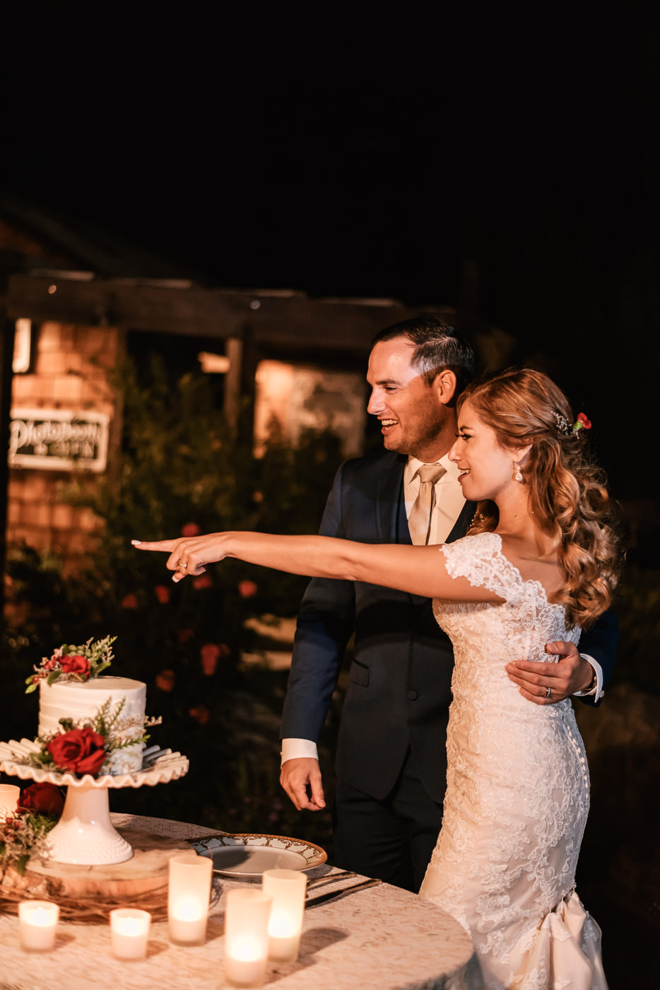 Bride points at one of her guests before cutting the wedding cake.