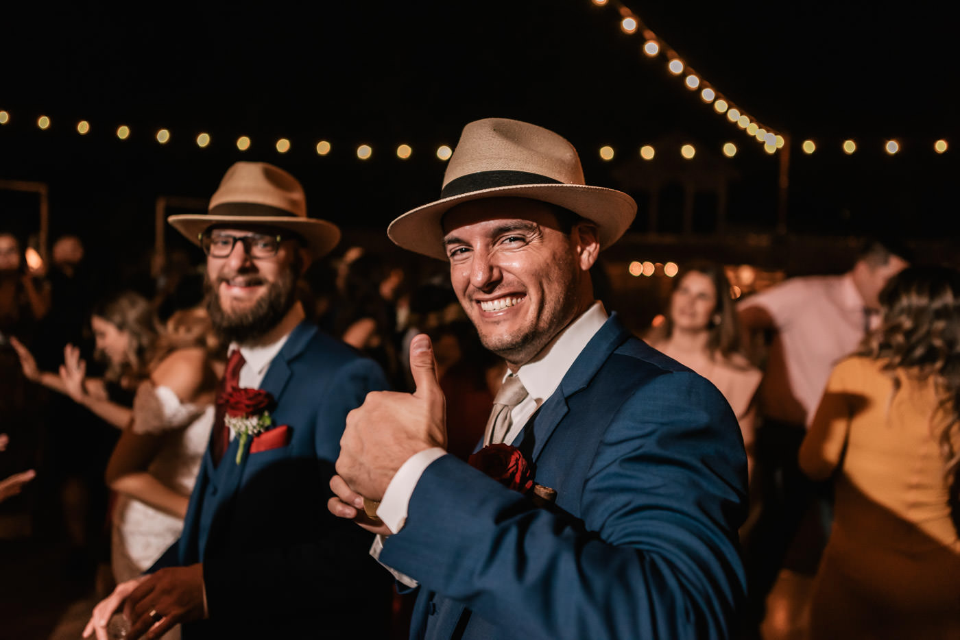 Groom gives a big smile and a thumbs up at the reception.